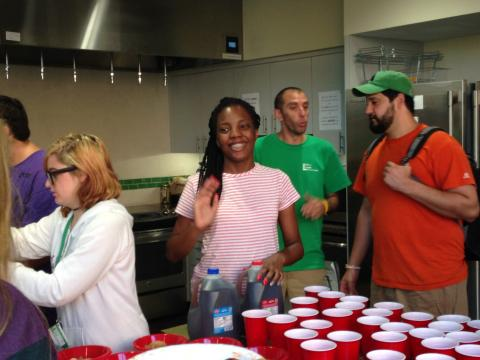 Participant waving and smiling, while filling up red cups.