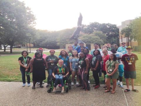 Group of participants in front of eagle statue at UNT.