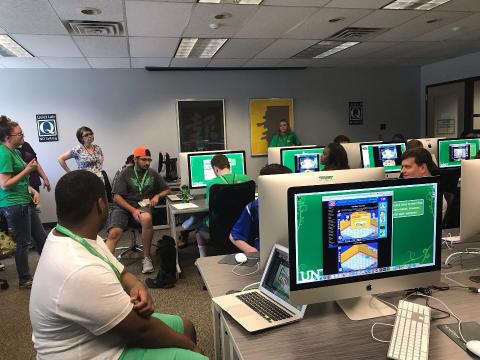 Group of participants, in a computer lab, listening to a guest speaker.