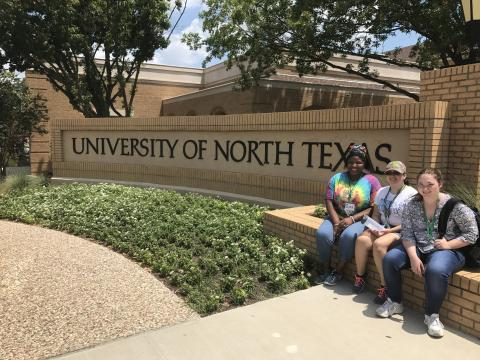Three participants outside of Bruce Hall, sitting by a UNT sign.