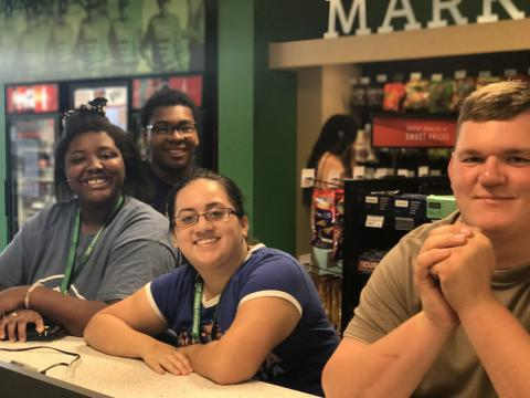 Four participants smiling at the UNT bookstore.