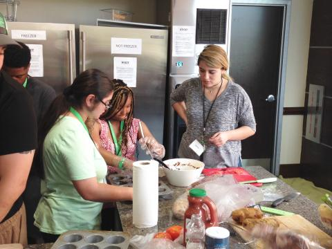 One staff and two participants preparing food in a mixing bowl.