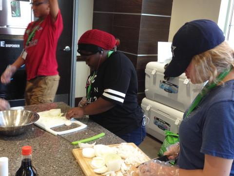 Group of participants slicing vegetables.
