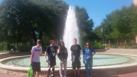 Group of five participants standing in front of a fountain at UNT.