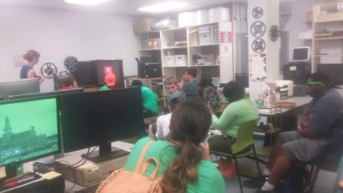Group of participants in a media lab, listening to a guest speaker.