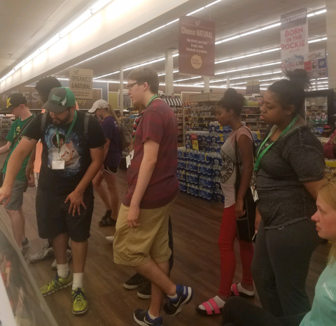 Group of participants at a grocery store, looking at food.
