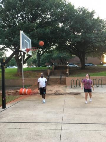 Two participants playing basketball outside.