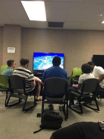 Five participants playing a video game on the television.